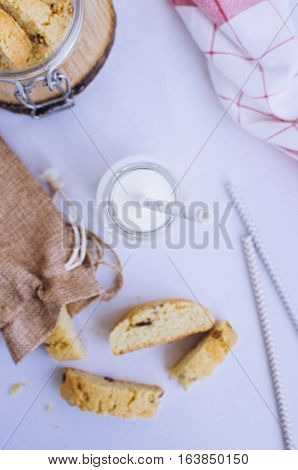 Homemade raisins cookies with bottle of milk on white background. Freshly baked raisin cookie. Healthy breakfast raisins cookies and milk. Tasty cookies for an afternoon snack. Top view.