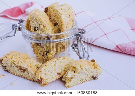 Homemade raisins cookies on white background. Jar with freshly baked raisin cookie. Healthy breakfast raisins cookies. Tasty cookies for an afternoon snack. Selective Focus.
