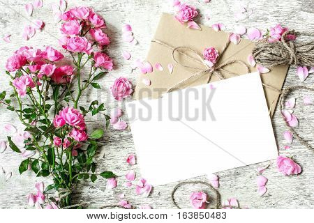 blank white greeting card with pink rose flowers bouquet and envelope with flower buds and rope on white wooden background. .top view. mock up