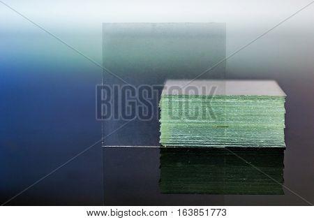Microscope coverslip glass reflecting on glass table closeup