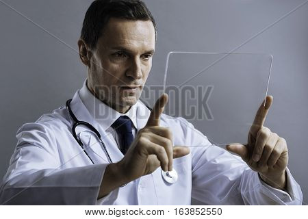 Proud of job. Handsome concentrated satisfied doctor posing with medical glass and discovering it attentively while standing on a grey background.