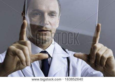 Proud job. Handsome concentrated attentive doctor looking at medical glass and discovering it attentively while standing on a grey background.