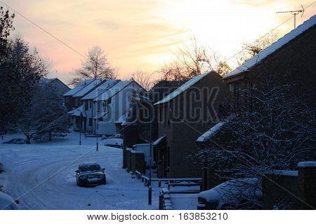 a snowy urban village road scene in winter