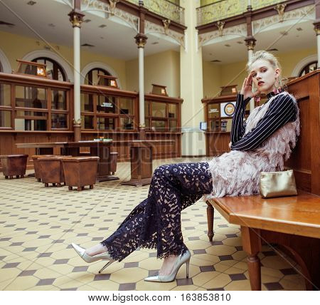 young attractive fashion lady on railway station waiting, vintage people concept in classic interior close up