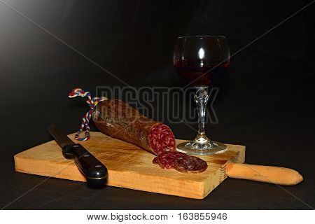 Still life with sausage and red wine