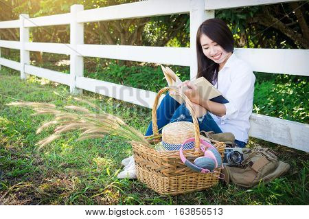 Pretty Relaxed Young Asian Woman Reading A Book At The Lawn Garen With Sun Shining, Vintage Tone