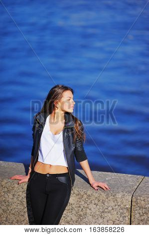 girl sitting on a parapet face exposed to the sun