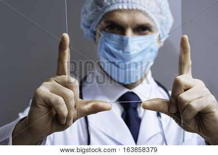 My view. Portrait of attractive confident delighted doctor in face mask looking through medical glass and wearing surgical scrub cap while posing on a grey background.