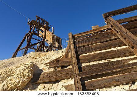 Old Wooden Mining Hopper Bin Under Blue Sky In The Nevada Desert Near A Ghost Town.