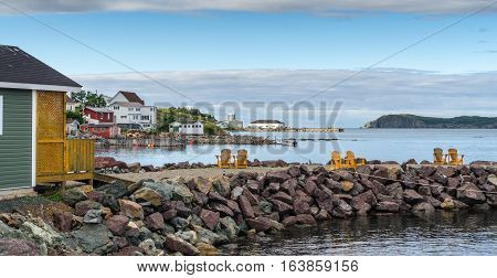 Golden Adirondack chairs on a rock jetty.   Houses on the sea along a village shoreline.  Rural Newfoundland, Canada.