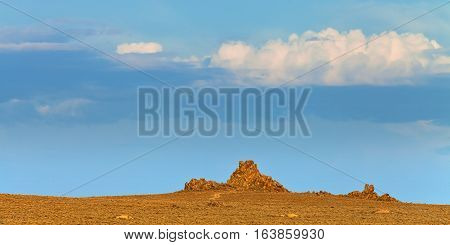 Nevada landscape at sunset near Lovelock NV. Tufa rock formations under blue sky.