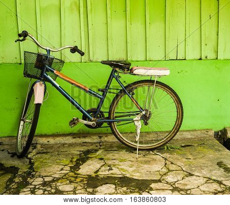 an old bicycle parked near green wall photo taken in Semarang Indonesia java