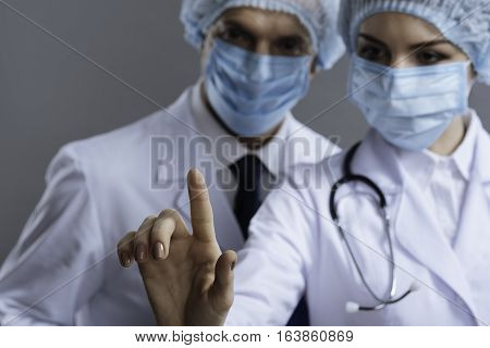 Work together. Delighted professional friendly colleagues using medical glass while wearing face masks and surgical caps and posing on a grey background.