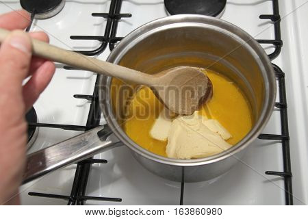 Melting Butter In A Pan With A Wooden Spoon On The Hob, Ready To Cook Flapjack