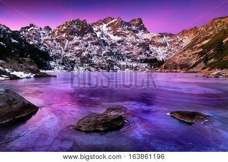 Sierra Buttes in winter with frozen icy lake and snow.