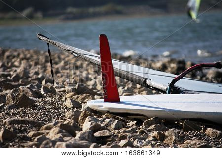 windsurfing board with fin upturned on a beach