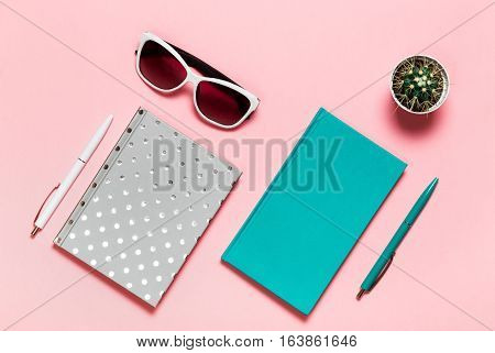 White and green-blue pen, glasses, silvery notebook, aquamarine diary, and cactus on pink background. flat lay, top view