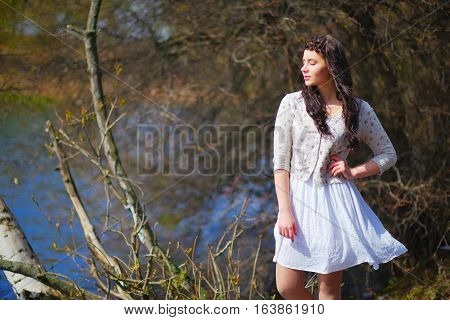 Wonderful portrait of a dreamy beautiful woman with silky hair braided in a pigtail in a white dress and jacket meditating on the lake with my eyes closed against the background of bare branches