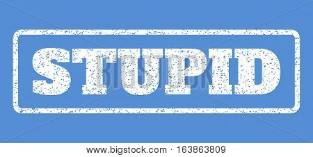 White rubber seal stamp with Stupid text. Vector message inside rounded rectangular frame. Grunge design and dust texture for watermark labels. Horisontal sticker on a blue background.