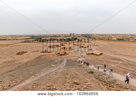 YAZD, IRAN - MAY 4, 2015: View of the tourists sightseeing the Tower of Silence disused buildings at the foot of the hills and new Zorastrian cemetery.