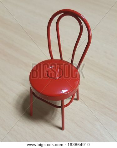 Red Metal Toy Chair on Wooden Table
