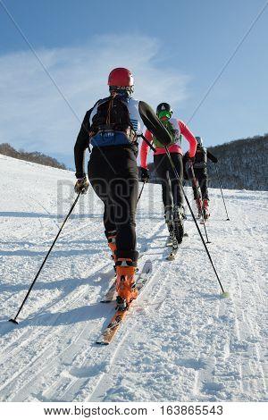 KRASNAYA SOPKA PETROPAVLOVSK-KAMCHATSKY CITY KAMCHATKA RUSSIA - FEB 4 2012: Group of ski-mountaineers climb the mountain on skis. Ski-mountaineering competitions - Cup Petropavlovsk-Kamchatsky.
