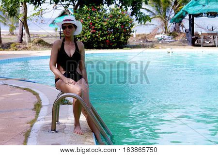 Lady pretty relax with swimsuit sit on pool in Chumphon province Thailand.