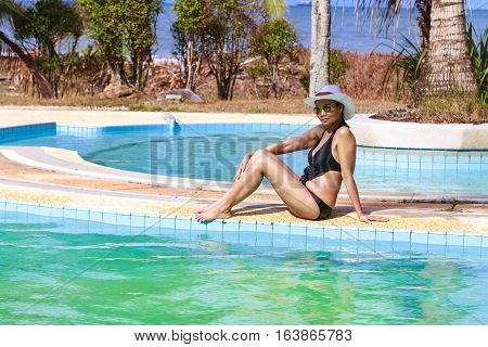 Lady body pretty relax with swimsuit sit on pool in Chumphon province Thailand.
