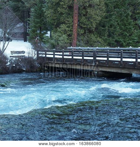 Snow covered road bridge over Wizard Falls on the Metolius River in Central Oregon in the forest on a winter day.