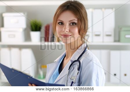 Smiling female medicine doctor filling in patient medical history list during ward round. Medical care or insurance concept. Physician ready to examine patient and help.
