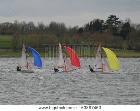 three sailboats racing under different colour spinnakers
