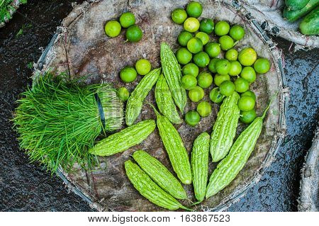 Momordica, Chinese Bitter Gourd Or  Cucumber, Greens And Limesin The Wicker Basket On The Vietnamese
