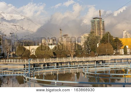 Tehran International Permanent Fairground Pool with Off Fountains Cityscape of Tehran and Alborz Mountains Covered by Snow at Background.