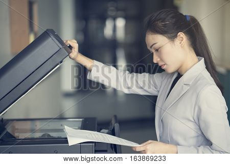 asian woman secretary using copy machine in the office