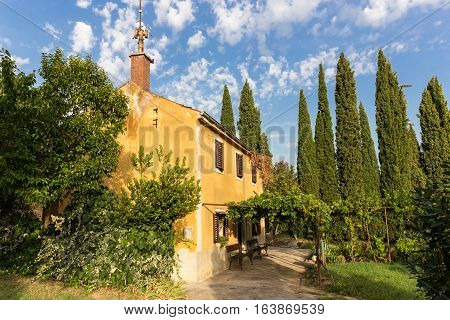 Beautiful traditional vintatge house with vine covered porch and cypresses trees growing in backyard. Portoroz, Slovenia.