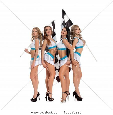 Sexy tanned girls dressed in formula one race style and high heel platform shoes posing cheerfully and flirty with flag in studio