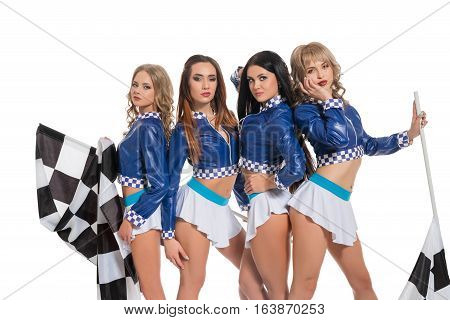 Sexy sunburnt girls dressed in formula one race style blue jackets, mini skirts and high heel platform shoes posing cheerfully and flirty with flag in studio
