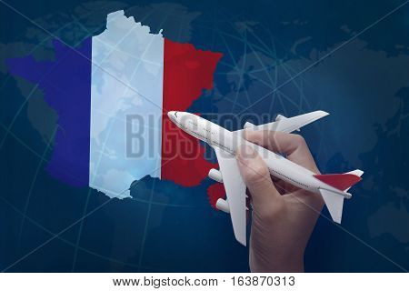 hand holding airplane with map of France.