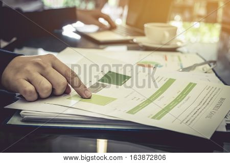 business man hand pointing stock market chart documents for discussing and using comupter laptop in office. vintage effect.