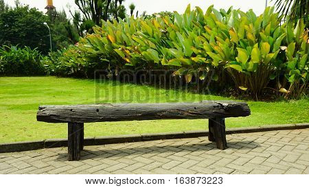 A single black wood bench in a garden photo taken in Semarang Indonesia java