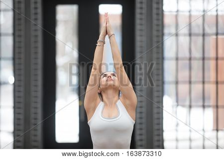Portrait of attractive young woman working out in luxury loft fitness center, doing yoga or pilates exercise. Beautiful model doing variation of Tadasana pose. Surya namaskar
