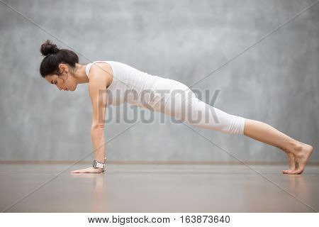 Beautiful young woman wearing white sportswear set and smartwatch working out against grey wall, doing yoga or pilates exercise. Push ups or press ups, Plank, phalankasana pose. Full length