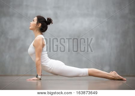 Beautiful young woman wearing white sportswear set and smartwatch working out against grey wall, doing yoga or pilates exercise. Upward facing dog pose, Urdhva mukha shvanasana. Full length
