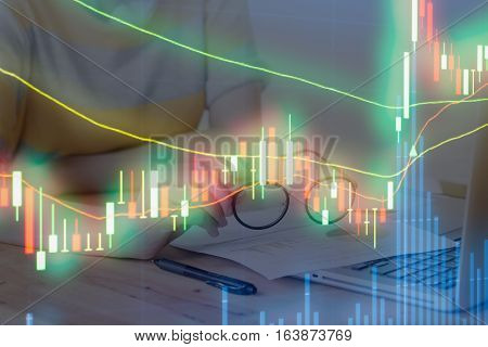 graph chart of stock market. background young girl hand holding spectacles with stock market and laptop in wood desk. Release concept.