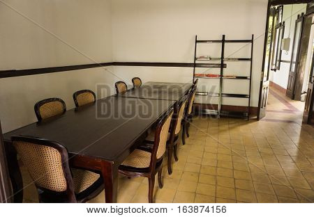 Set of large table and chairs in the middle of a room at Lawang Sewu photo taken in Semarang Indonesia java