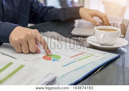 business man hand pointing documents for discussing and using comupter laptop. vintage effect.