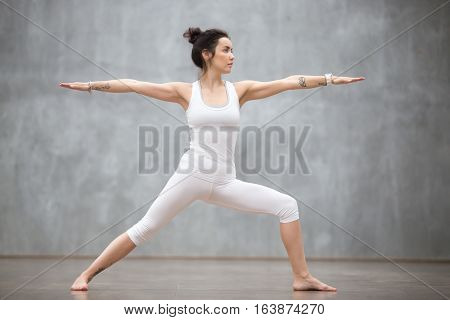 Side view portrait of beautiful young woman wearing white tank top working out against grey wall, doing yoga or pilates exercise. Standing in Warrior two pose, Virabhadrasana. Full length