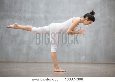 Side view portrait of beautiful young woman wearing white tank top working out against grey wall, doing yoga or pilates exercise. Standing in Warrior three pose, Virabhadrasana 3. Full length