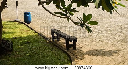 an empty blackwood bench near a garden at Lawang Sewu photo taken in Semarang Indonesia java