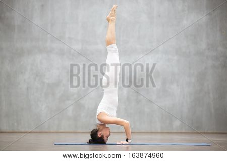 Portrait of beautiful young woman wearing white sportswear working out against grey wall, doing yoga or pilates exercise. Headstand, salamba sirsasana II. Full length photo